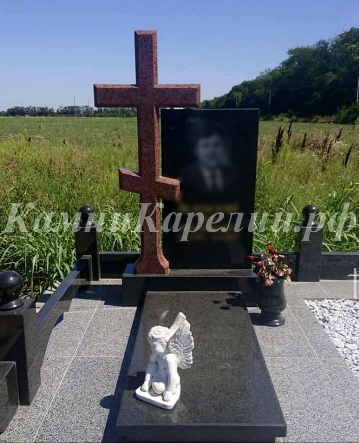 Вертикальный гранитный одиночный памятник с крестом из красного Лезниковского гранита также включает элементы, вырезанные из карельского габбро-диабаза высокой твердости.