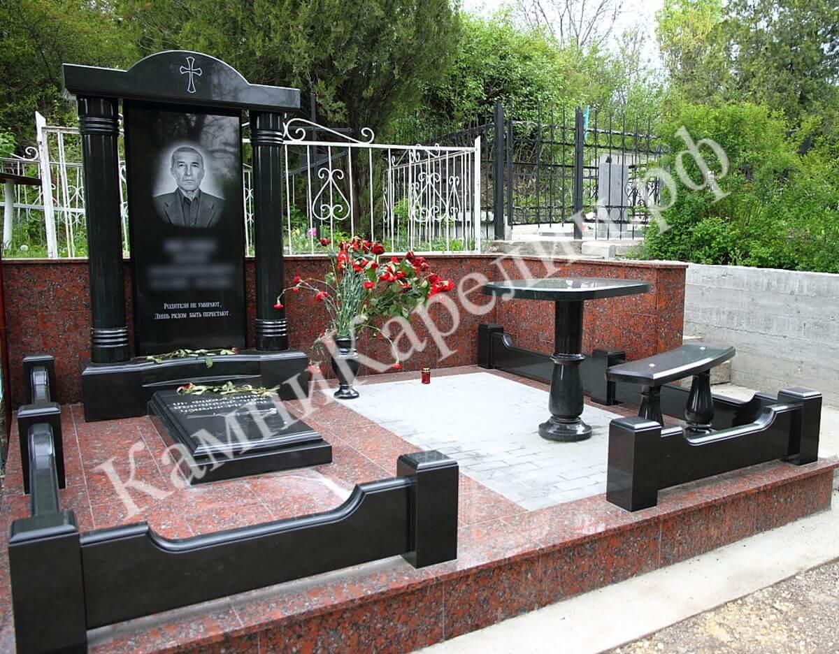 Одиночный вертикальный гранитный памятник на могилу изготовлен из чёрного габбро-диабаза. Элементы отделки и остальной композиции также используют коричневый Ладожский сорт гранита.