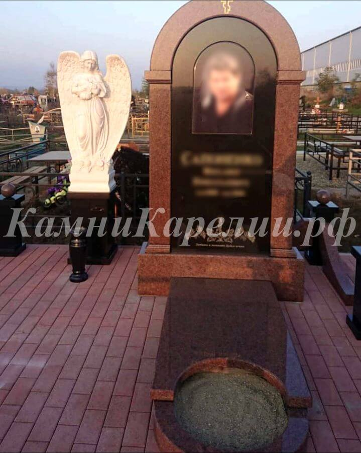 Вертикальный гранитный одиночный памятник изготовлен из пёстрого Лезниковского гранита. В состав композиции также входит композитная фигурка скорбящего ангела. Комплекс имеет необычную круглую клумбу.