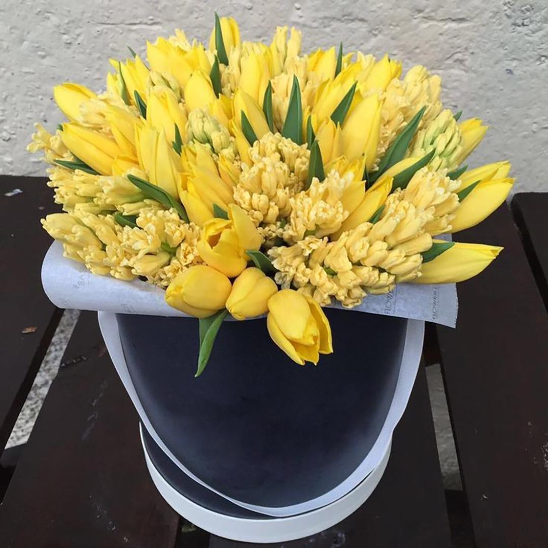50 желтых тюльпанов и 25 желтых гиацинтов в коробке в руках
