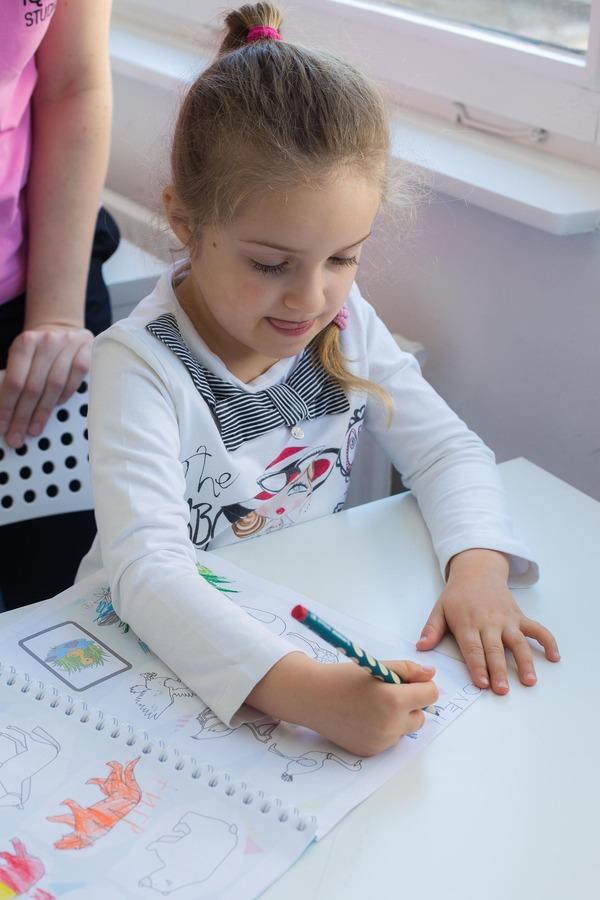Ребёнок держит карандаш и выполняет задание