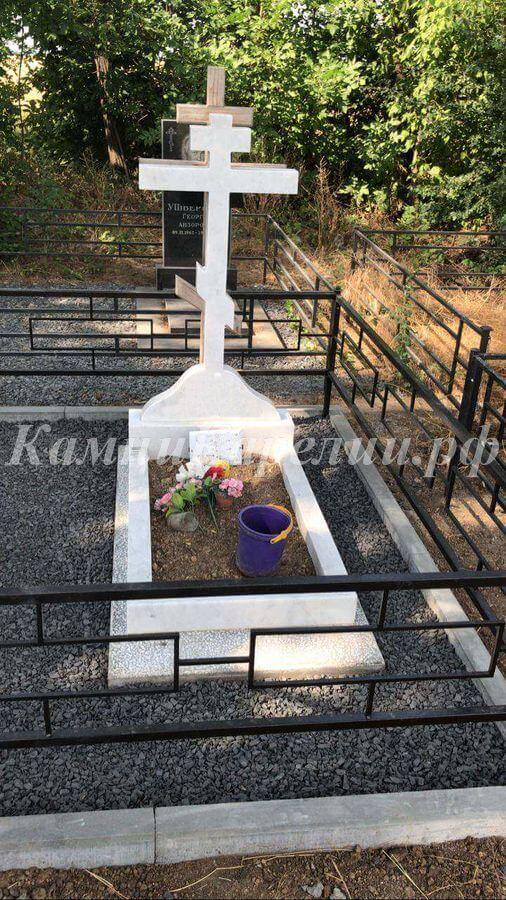 Вертикальный гранитный памятник с крестом изготовлен из белого композитного материала. Подложка надгробной части вокруг клумбы сделана из Покостовского светлого гранита.