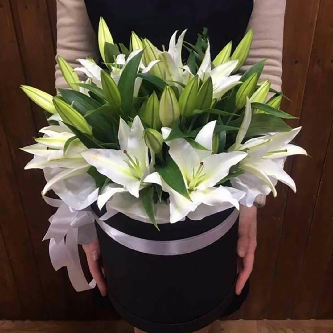 Белые лилии в коробке в руках