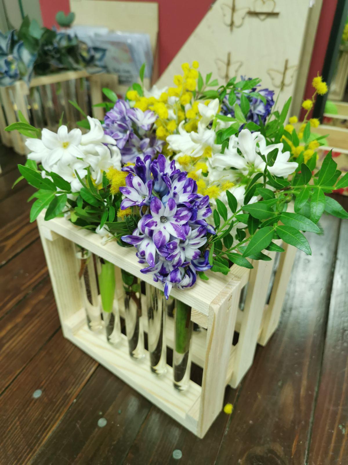 Цветы в колбе с мимозой и хелеборусом
