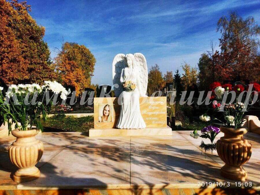 Горизонтальный одиночный гранитный памятник и отделка изготовлена из заграничного желтого сорта гранита. На надгробном камне сидит фигура скорбящего ангела. В комплекте присутствуют два вазона.