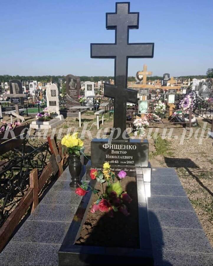 Вертикальный гранитный одиночный памятник с крестом в чёрном обрамлении изготовлен из карельского габбро-диабаза. Отделка постамента создана из плитки Покостовского гранита.