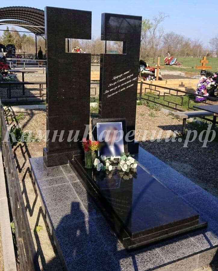 Вертикальный гранитный одиночный памятник с прорезным крестом изготовлен из чёрного габбро-диабаза. Пестрая разновидность этого камня использована для создания отделки и остальных частей композиции.