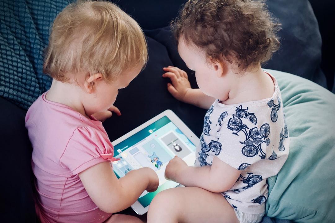 два ребёнка заняты электронным устройством