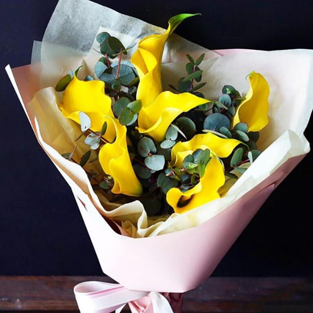9 желтых калл с эвкалиптом в руках