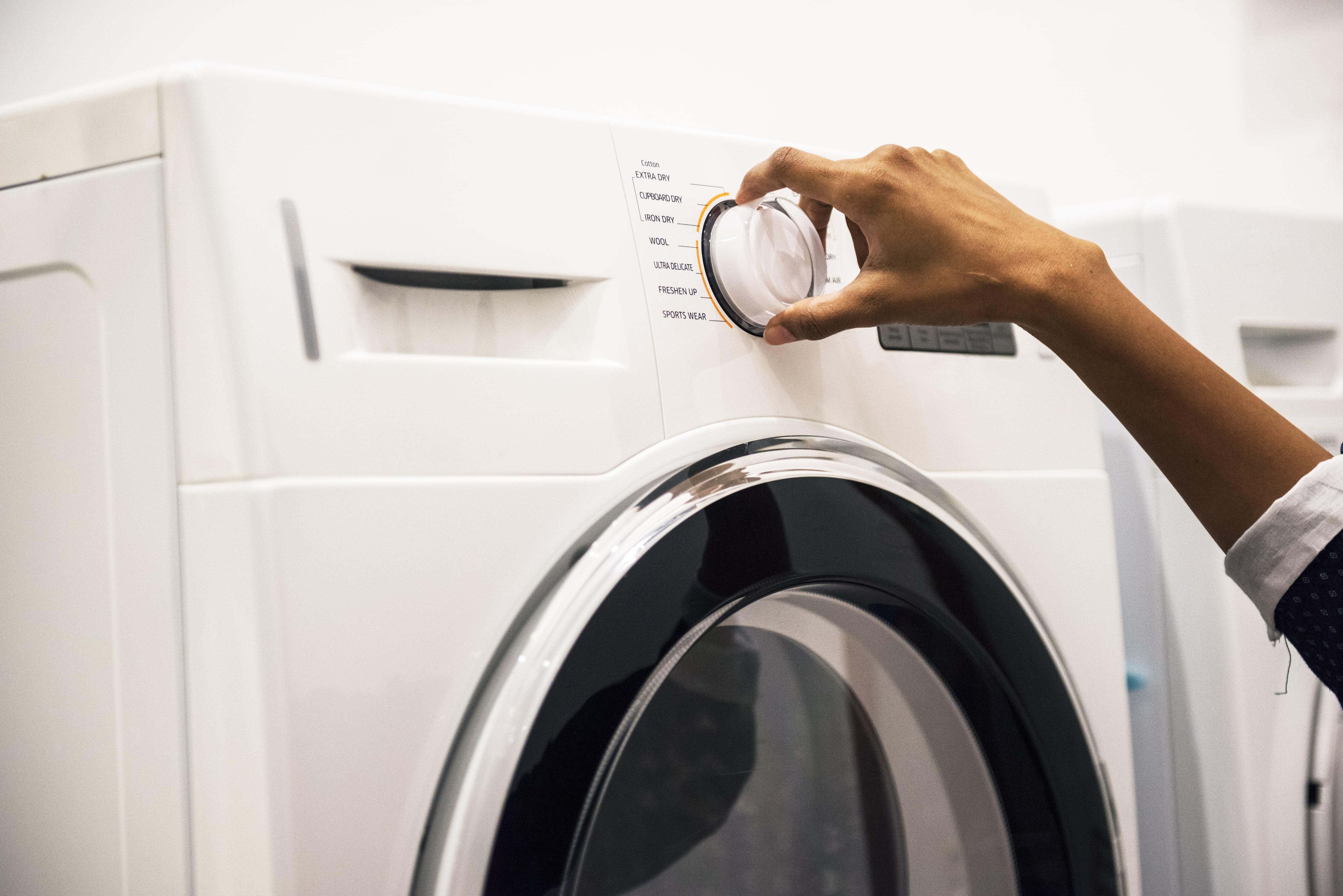 Мастер по ремонту стиральных машин пробует включить стиральную машинку повернув регулятор