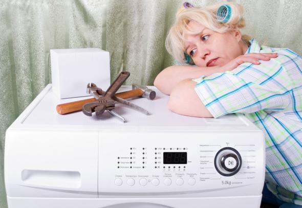 женщина ждёт мастера стиральной машинки подготовив инструмент и оперевшись на стиральную машинку